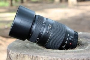 A 300mm DSLR lens placed on a stump with a round lens hood attached.