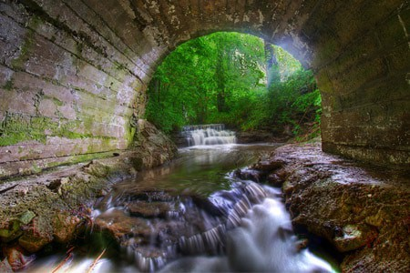 Landscape photo of a waterfall underneath a bridge in Nauvoo.