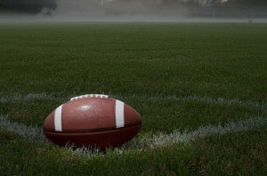 stock photo of a football sitting on a green grass field