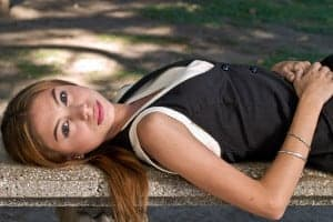 Woman lying down to hide flaws during a portrait photography session