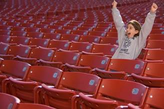 A woman cheering for victory in an empty stadium with red seats.