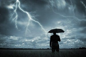 Interesting photo of a guy standing in a field near lightning.