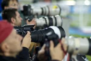 A side-view of many sports photographers with various lenses on their DSLR cameras.