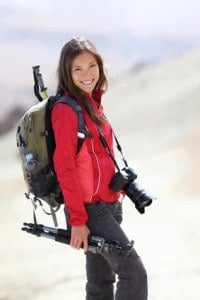 A beautiful female photographer holds a tripod and a DSLR while hiking and camping.