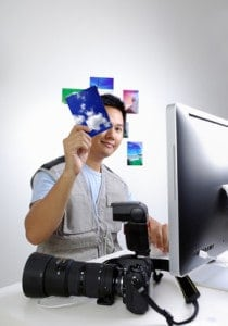 A male holding pictures in front of his face while wearing a photo vest next to a Mac computer.