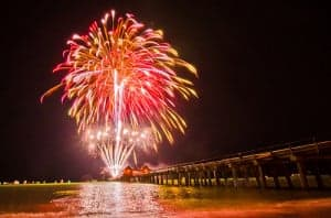 Red fireworks exploding over the pier in Naples, Florida