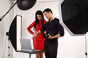 Photographer gives tips to a model during a studio shoot with lighting mods.