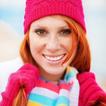 A vibrant and colorful photo of a woman wearing a winter hat and scarf.