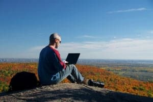 Photographer uses a computer to apply effects on photos while sitting on a mountain.