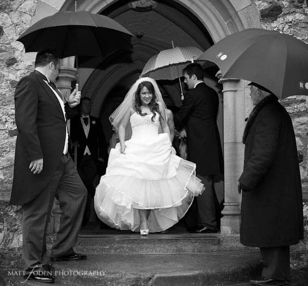 Wedding photo of a bride leaving the church with umbrellas raised around her.