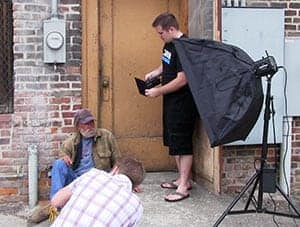 Behind the scenes of a photoshoot of a man on the street.