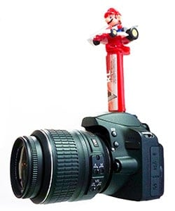 Candy dispenser on the hotshoe of a camera.