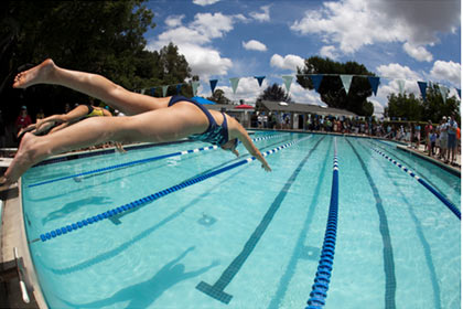 Female swimmer diving into a pool from a diving block, as shot with a fisheye lens.