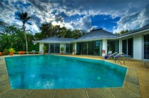 HDR photo of a pool in someone's backyard behind their house in Florida.