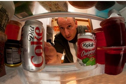 Wide-angle lens shot of a guy reaching into a refridgerator and getting food.