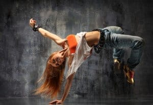 A dancer does a move with her hand on the ground.