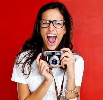 Photographer holding a camera on a red background.