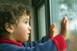 Portrait photo of a boy looking out through a window at a rain storm.
