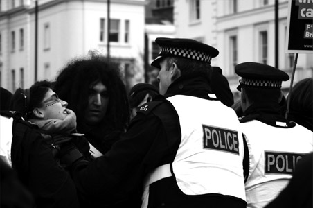 Photo of a riot in the UK with police shoving people.