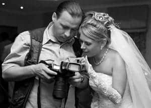 Bride and photographer looking at a camera