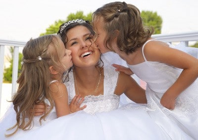 Two little girls kissing a bride on her wedding day
