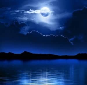 Clouds partially covering the moon over a lake.