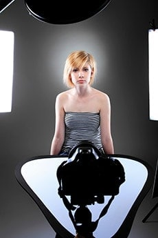 Model with short hair in a photo studio with lighting modifiers around her.