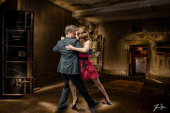 Two models tango dancing in a grungy environment.