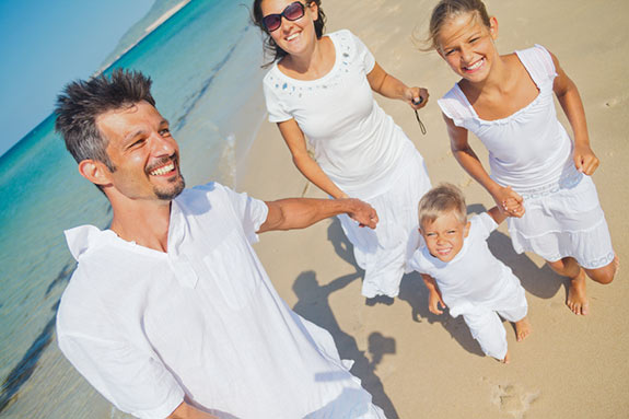 Family wearing all white clothes for a photo shoot on the beach.