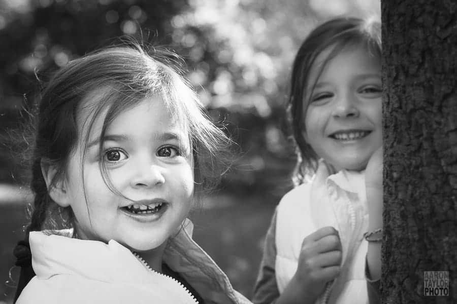 With posing done long ago, I just told these sisters to run around their backyard. They did cartwheels, played tag, and hid behind trees. Chasing them with the camera was a game in itself, a worthwhile game when this great candid shot was captured.