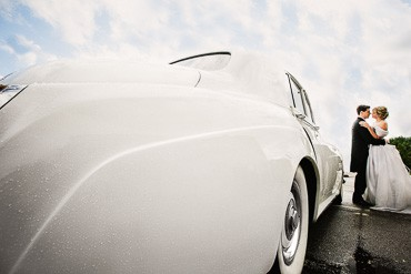 A photo of a bride and groom next to their vintage Bentley