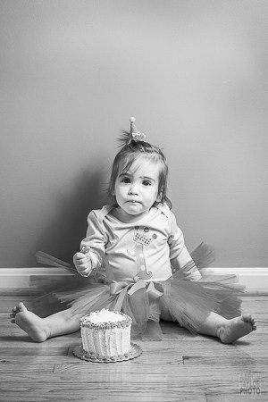 This photo was taken in a small hallway in order to use simplicity of the wood floor and the bare wall. Since the space itself is blank, we can focus on the little girl and her cake.