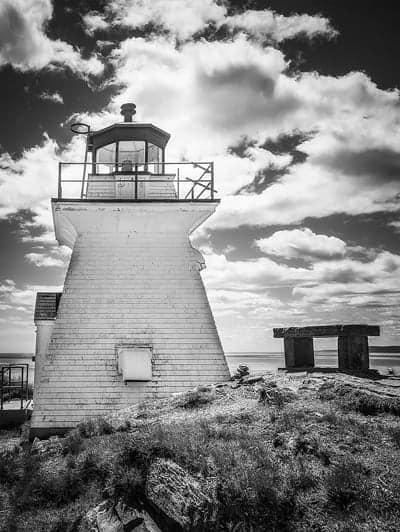A black and white photo of the Cape Enrage Lighthouse in New Brunswick.