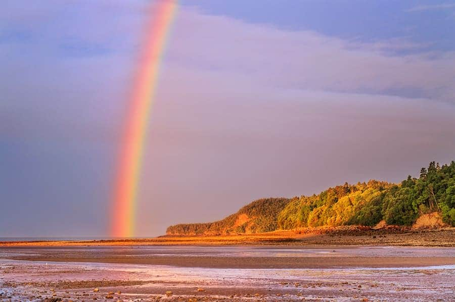 A photo of a rainbow at sunrise, over Alma Beach, just outside Fundy National Park, New Brunswick.
