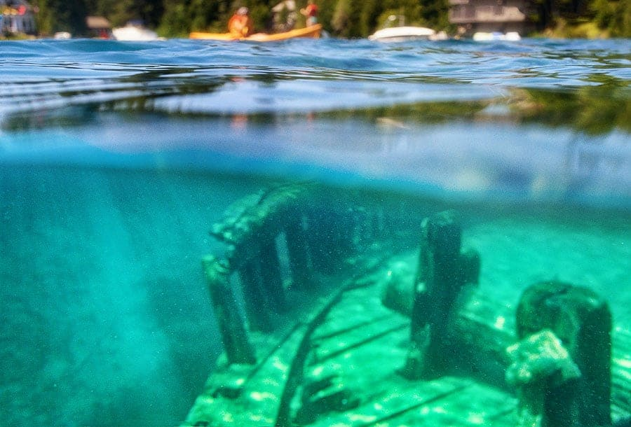 A photo of a shipwreck below the surface and paddlers and cottages above, in Tobermory, ON.