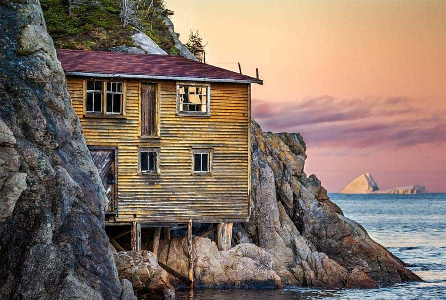A photo of the iconic yellow house on the rocks in Shoe Cove, Newfoundland. Photo by Tracy Munson