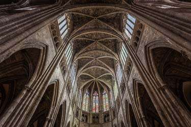 The interior of the stunning Bordeaux Cathedral in France showing the stained glass windows and the rear end photographed from the central cross location. Rick McEvoy Photography - architectural photographer