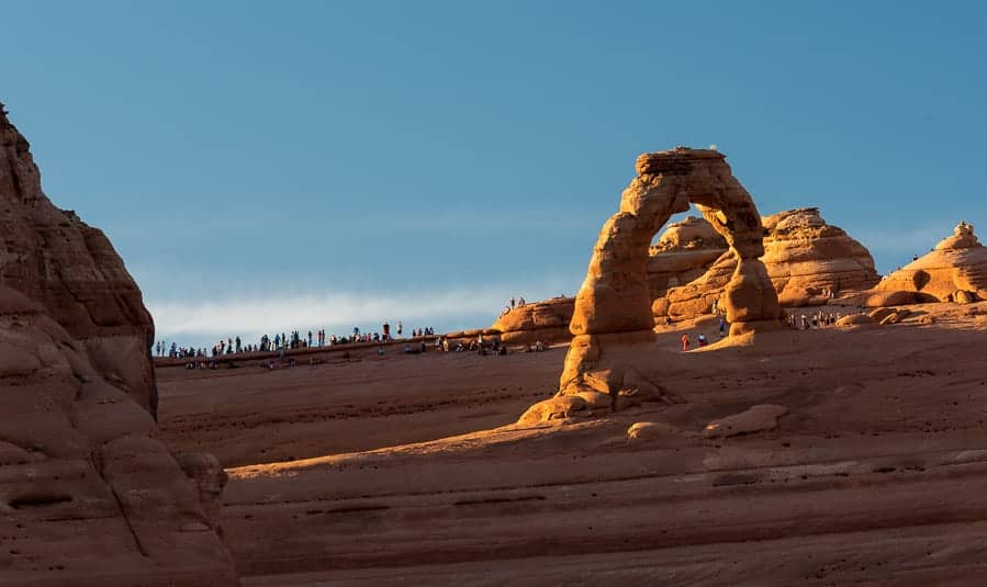 People line the rim around Delicate Arch as sunset nears.